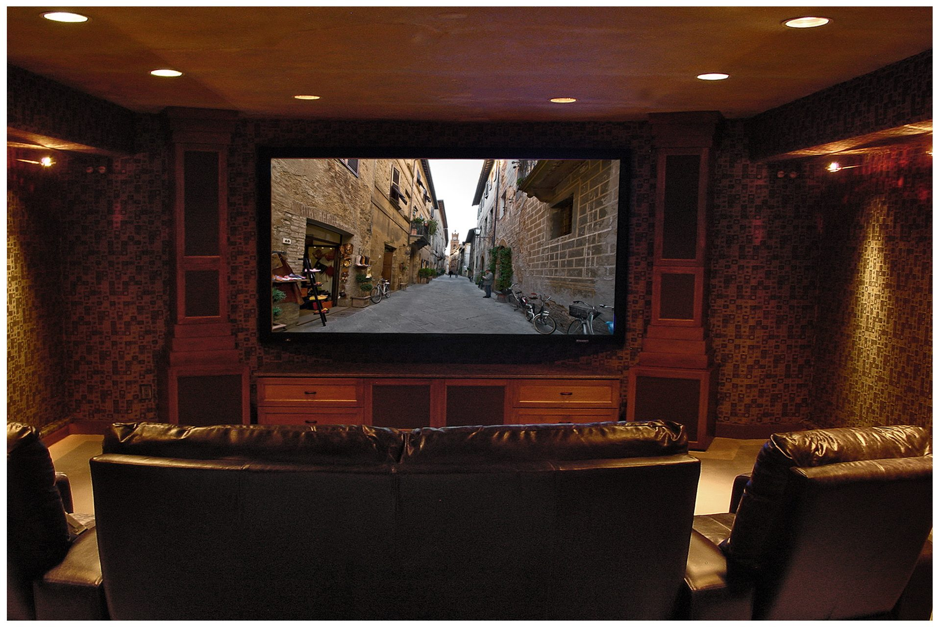SMALL THEATER IN A DEDICATED ROOMCabinet towers flanking the screen enclosed all front subwoofers and main speakers.  A fixed projector above & behind seating area remained fairly invisible; side speakers were recessed into concrete basement walls flanking the viewing area, and a second pair of in-ceiling surrounds was recessed behind the viewing area. All electronics were placed in a closet space in an adjacent room.