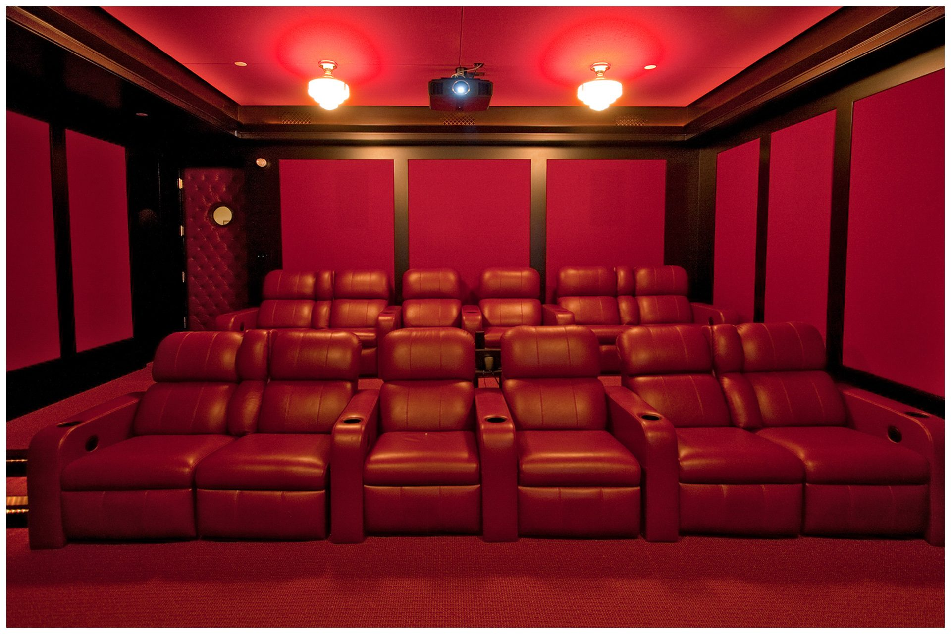 DEDICATED BASEMENT THEATER 12 seat dedicated basement theater with Acoustic paneling to limit sound intrusion outside the room. Front Speaker elements are enclosed into cabinetry and all other  speakers are placed under acoustical panels.Screen and seating are placed on the right side of the room to allow a wide isle leading to exit door in so doing, seats in the center are centered on the screen and front speakers.System is enclosed in an adjacent closet. JBL Synthesis speakers elements are hidden behind fabric in custom wall panelings.