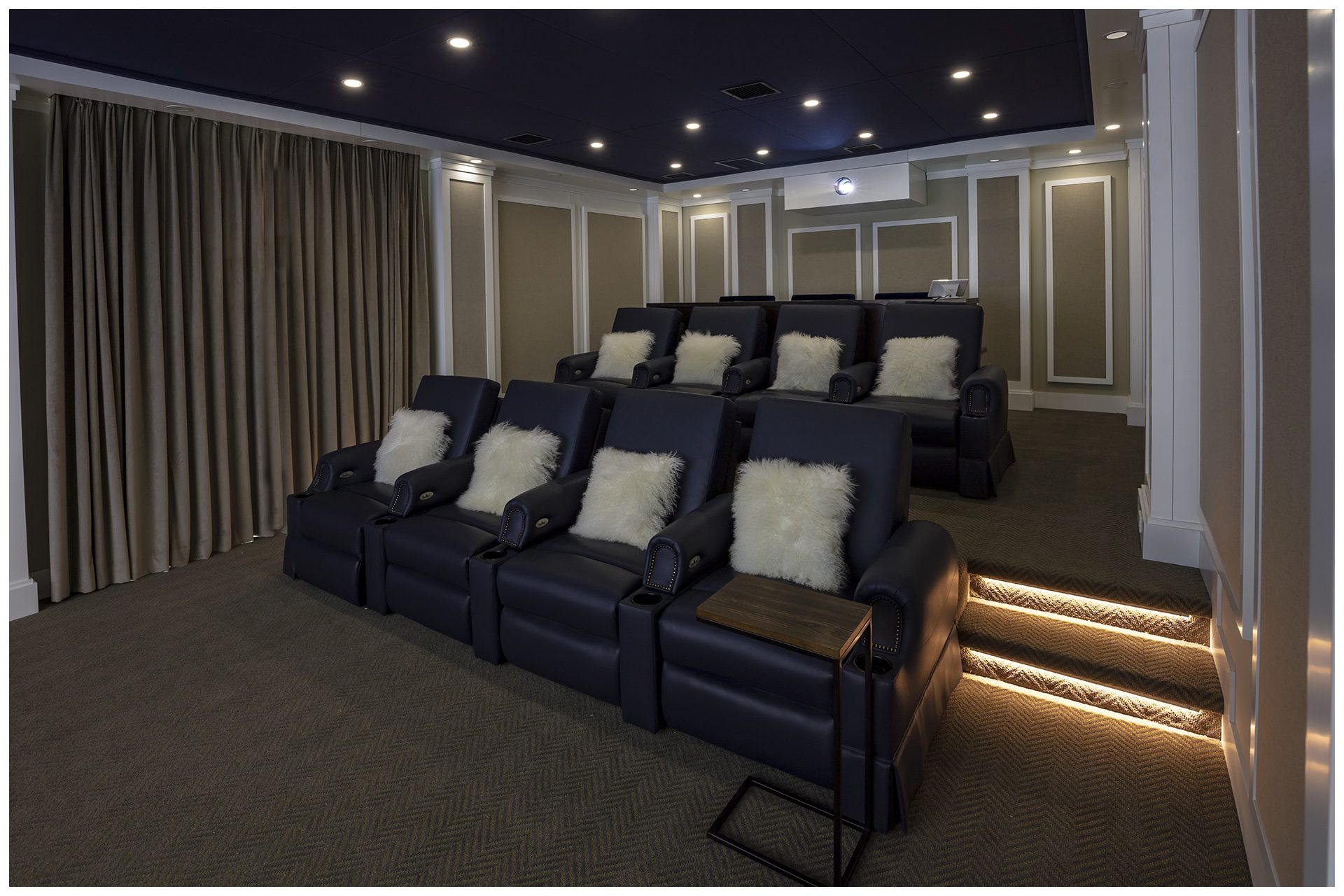 THEATER IN A DEDICATED ROOMProjector is enclosed in a sealed enclosure in the back to prevent projector noise to be audible in the room.  Electronic side drapes allow day light to come in as this room is on the main floor of the residence and owners wished for it to remain bright, open and inviting when theater is not in use.