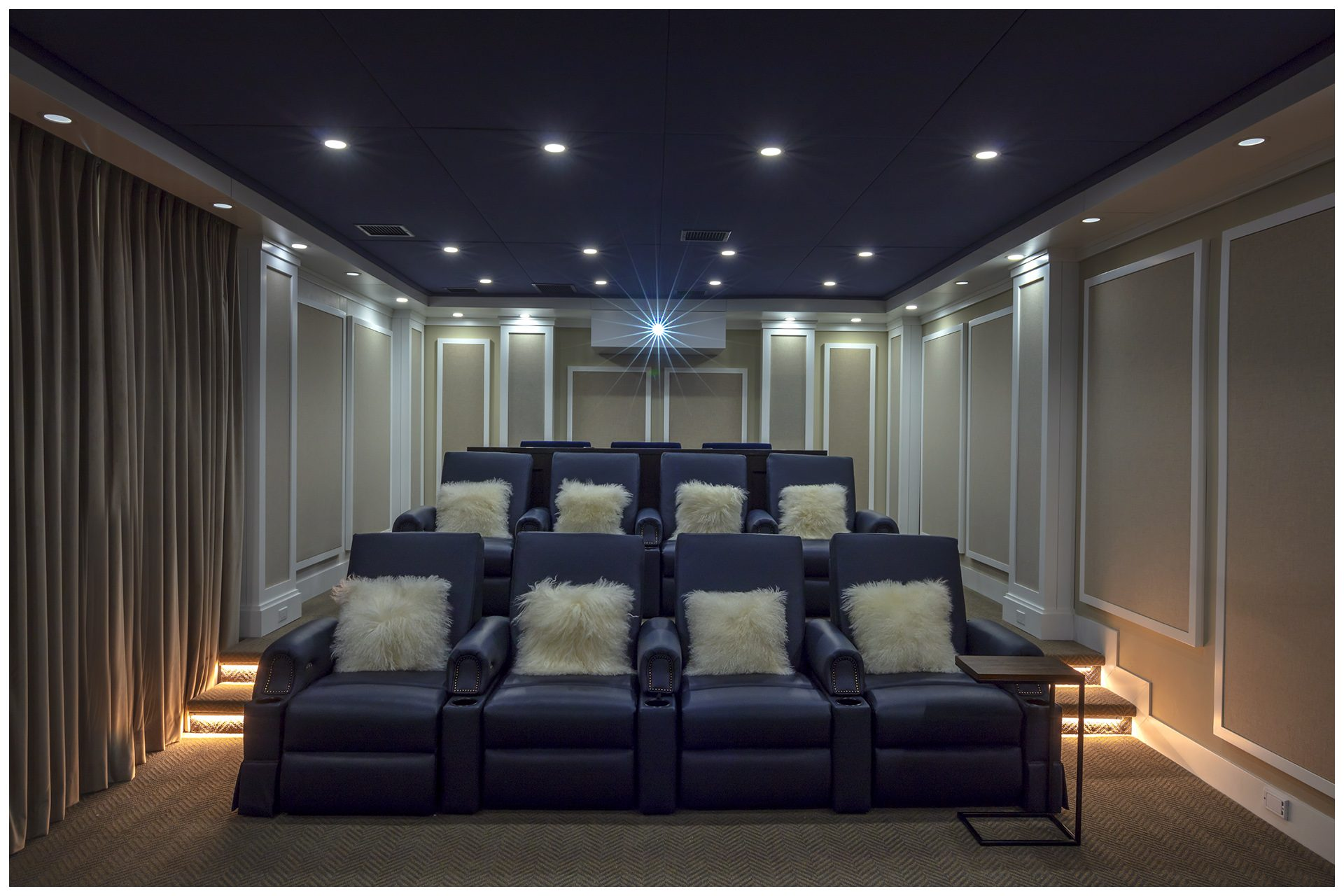 THEATER IN A DEDICATED ROOMHidden panels in the rear open to system elements where the owners are able to insert a DVD locally.  Four sets of lights offer several modes of lighting for the room. JBL Synthesis speakers elements are all enclosed behind fabric in custom paneling from Acoustic Innovations.